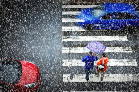 UOMO pioggia: attraversamento pedonale con auto la nevicata