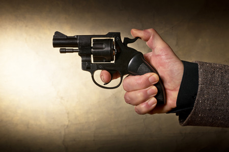 Silhouette of a mans hand with a handgun in brown photo