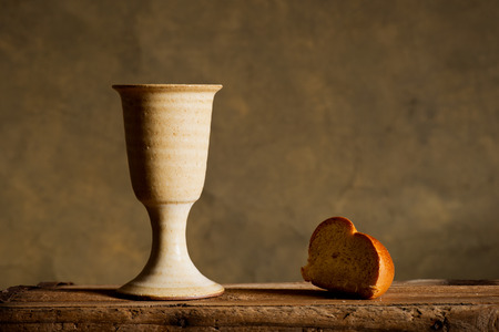 communion: chalice of wine and bread on the dark background