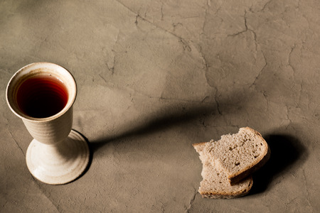 pan y vino: cáliz de vino con pan en la mesa Foto de archivo
