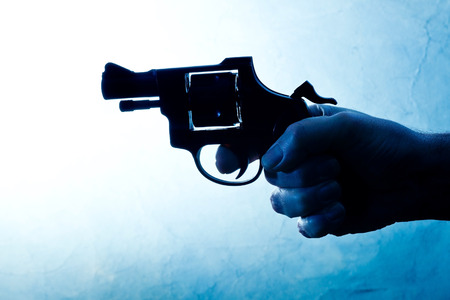 Silhouette of a mans hand with a handgun in blue photo