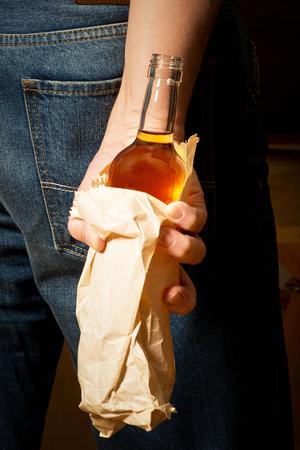 hard drinker hides  bottle in a paper bag photo