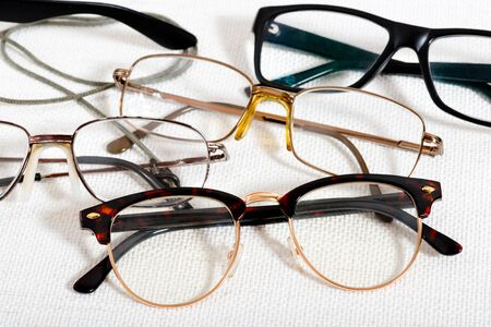 A lot of reading glasses on the white table Imagens