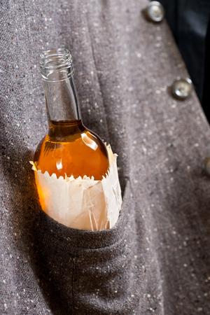 the drinker: hard drinker hides  bottle in his pocket