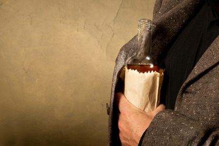 the drinker: hard drinker with a bottle in the paper bag Stock Photo