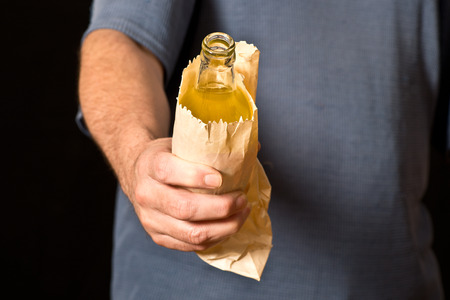 drinker: drinker holds a bottle in the paper bag, shallow depth of field