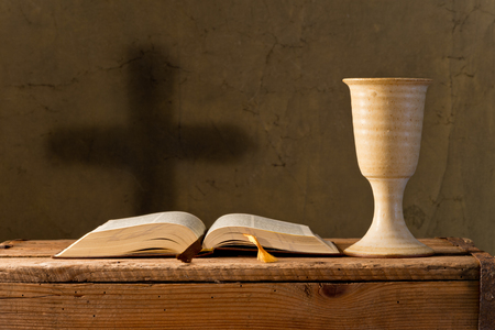 old church: open bible with chalice of wine in the church,selective focus Stock Photo