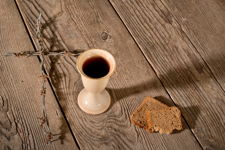 chalice bread: Chalice, bread and cross on the wooden table