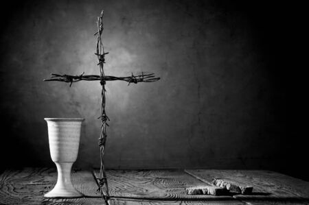 ascetic: Chalice, bread and cross on the wooden table