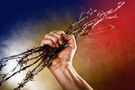 prisoner of war: man crushes a bundle of barbed wire Stock Photo