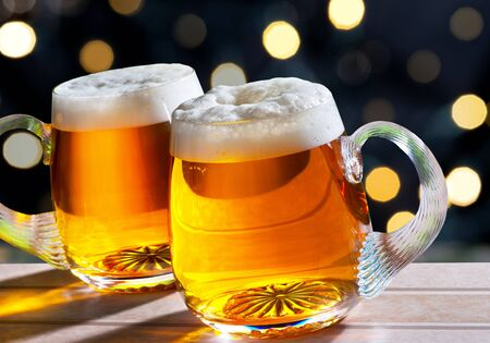 filled: two beer glasses with colored light on the background