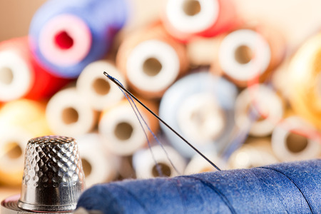 workroom: detail of a needle with thread in the workroom,shallow depth of field Stock Photo
