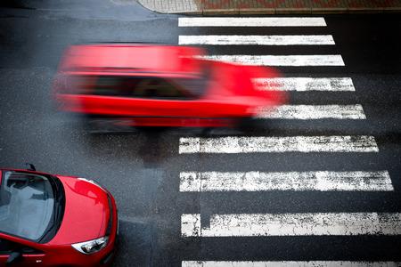 twee rode auto's op de voetgangersoversteekplaats, Stockfoto