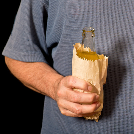 the drinker: drinker holds a bottle in the paper bag, shallow depth of field