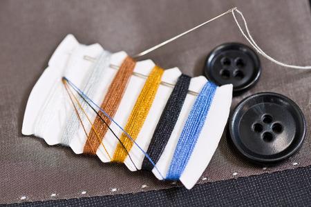 kit de costura: detalle de kit de costura en la ropa de color gris Foto de archivo