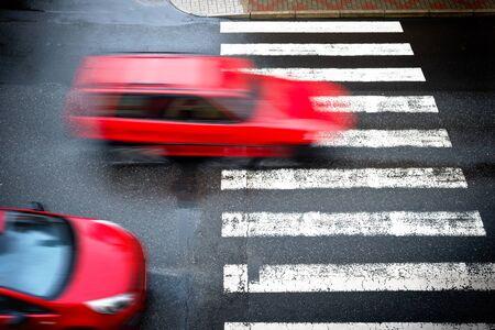 twee rode auto's op de voetgangersoversteekplaats,