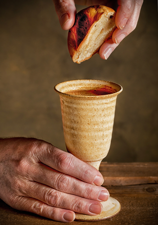 last supper: chalice of wine and bread with hands of reverend