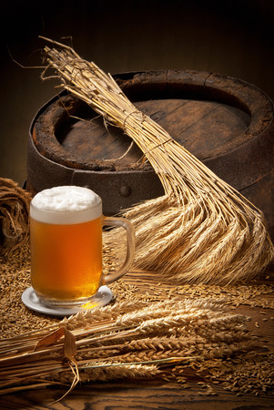 wooden barrel: glass of beer with barley and wheat on the wooden barrel