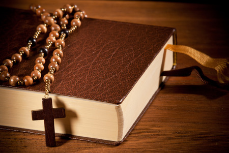 closed book: closed book with rosary on the wooden desk