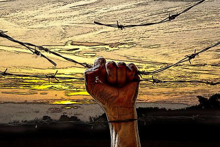 prisoner of war: hand behind barbed wire with sunset in the background Stock Photo