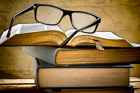 reading glasses: illustration of open book with reading glasses in the bookshelf