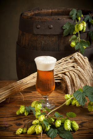 hop cone: glass of beer with hops and old barrel Stock Photo