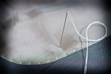 suture: detail of a needle on the gray clothing Stock Photo