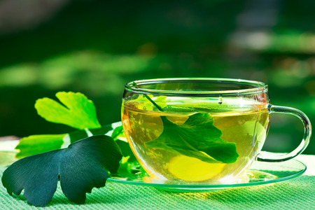 herbaceous: glass of herbaceous tea with ginkgo leaves Stock Photo