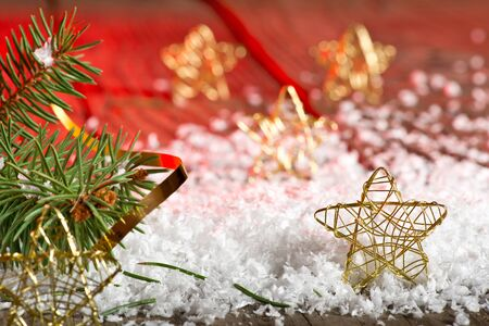 Christmas stars and needles in the snow with red background