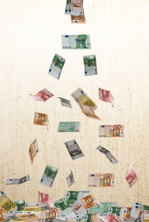 coin toss: falling of euro currency on the unfocused background Stock Photo