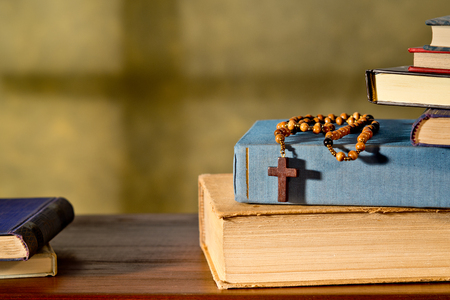 humble: still life with books and rosary in the church Stock Photo