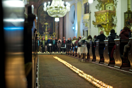 church people: Line of flaming candles in the baroque church