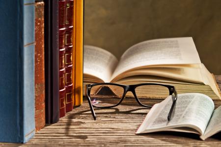 humilde: gafas de lectura con bokks sobre la mesa Foto de archivo