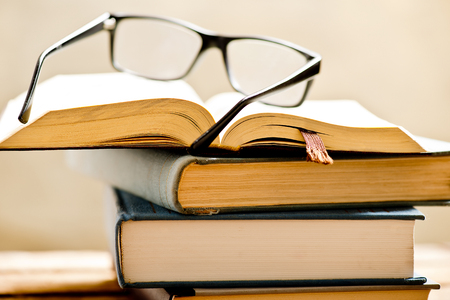open book with reading glasses in the bookshelf, shallow depth of filed Banque d'images