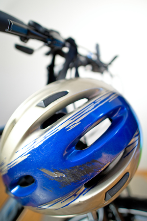 spokes: Old Scraped Safety Helmet On The Bike Stock Photo