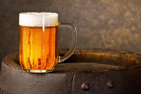 Glass of Beer on the Old Wooden Barrel.