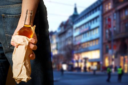 Drinker hiding bottle of spirits in the paper bag
