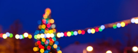 Christmas background with unfocused Christmas tree by night Stock Photo