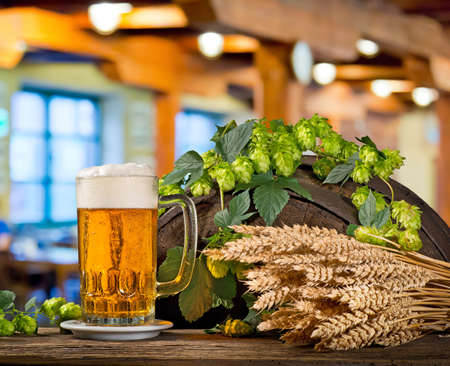 Glass of beer with hops and barley on the wooden barrel