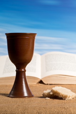 Open bible with chalice of wine and bread Stockfoto