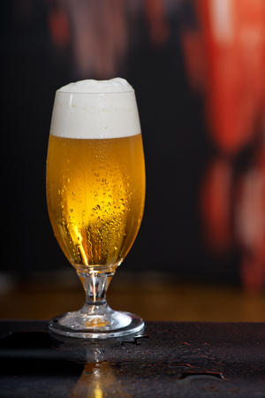 Glass of beer on the dark background