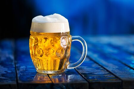 Glass of beer on the blue wooden background. Imagens