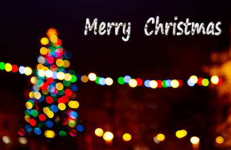 Dark background with Christmas tree and writing Merry Christmas