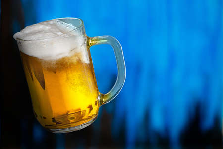 Glass of beer on the blue background