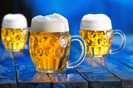 Glasses of beer on the blue wooden background.