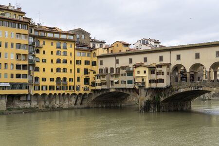 architecture and buildings: Ponte Vecchio and other similiar architecture buildings over the river.