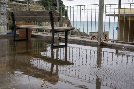 spezia: A small bench and patio area covered in rain water looking over the riomaggiore station Stock Photo