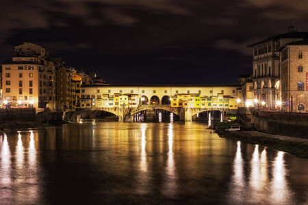severe weather: Ponte Vecchio and the buildings close by at night reflecting on the river Arno .