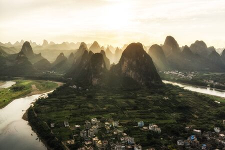 The view of sunset from laozhai shan in near xingping, guangxi, china. Taken during hot summer. xingping is near yangshuo. The view of karst mountains and hill tops.