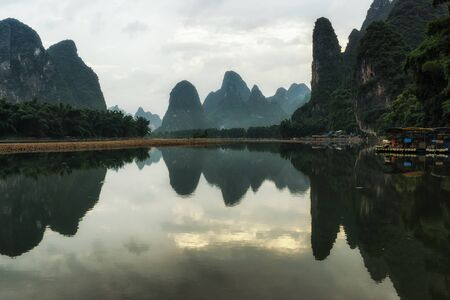 The morning sunrise view over li river with clouds and fogs surrounding the karst mountain tops. Xingping, Guangxi, China 写真素材